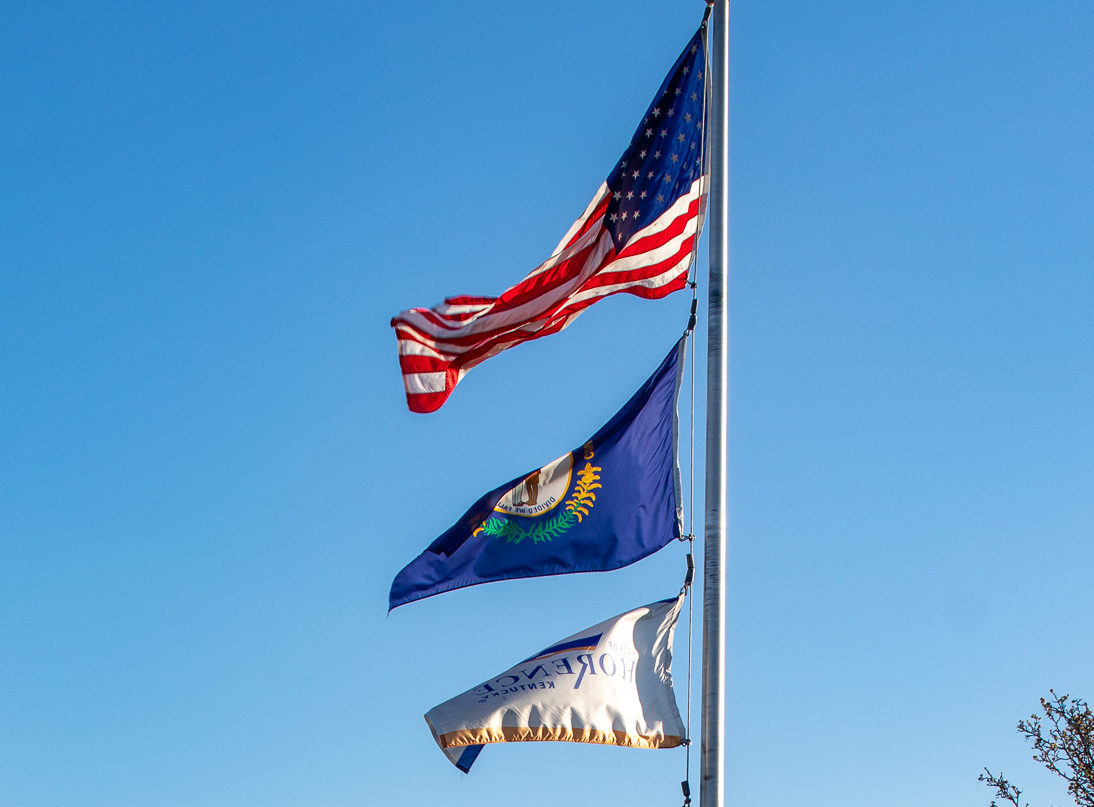 flag pole with the american flag, Kentucky flag, and city of Florence flag